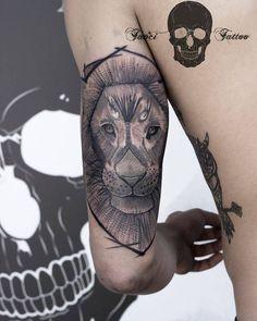 Tatuaje de estilo sketch de un león situado detrás del brazo izquierdo.