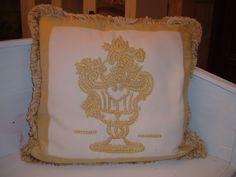 Cuscino barocco con decorazione floreale monocromatica oro.