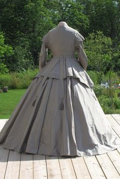 """A rare, authentic 1860's replica gown taken directly from a French antique design, but in a wearable modern size. Made of luxurious 100% silk taffeta in a steel blue and """"old gold"""" stripe, this is a 2-piece ensemble consisting of the princess-seamed dress and a separate decorative peplum. Almost 12 yards of costly silk went into the construction of this gown. Except for the sizing, the result is almost exactly like the 1866 original. The dress is intended to be worn over mid-Vic..."""