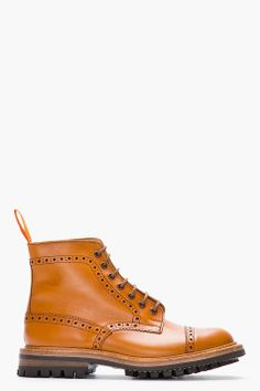 JUNYA WATANABE // TAN LEATHER QUARTER BROGUE SUPER BOOTS 31253M047002 High top leather quarter brogue boots in tan. Round toe. Tan lace up closure with brown eyelets. Signature perforated detail and serrated edges throughout. Twill pull loop at heel collar in orange. Genuine Goodyear welt. Thick rubber lug sole in black. Tone on tone stitching. Produced in collaboration with Tricker's of England. Leather upper, rubber sole. Made in United Kingdom.