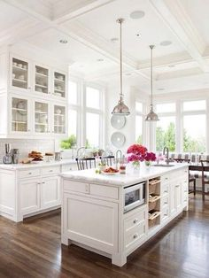 White french country kitchen with marble island bench with storage, industrial polished nickel pendant lights lamps, white subway tiles