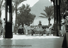 On the Mena House terrace, pretending not to notice the Pyramid.