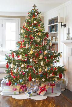 Großer Christbaum mit viel Schmuck, schön verpackte Geschenke unter dem Baum, Weihnachten zu Hause