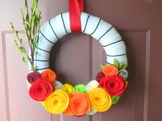 Dollar Tree wreath form, yarn, easy diy felt flowers. 1hr and $5 or less! Endless possibilities  color/flower style combos!!
