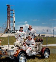 With the Apollo 17 Saturn V launch vehicle in the background, the crew is photographed with a lunar roving vehicle trainer. Eugene Cernan is seated with Harrison Schmitt, standing on the left, next to Ronald Evans.