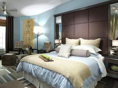 """After: Eco-Friendly Cool    Candice chooses a low-VOC paint in a warm blue color, a mix of organic fabrics and recyclable carpet tiles as some of the environmentally friendly elements in this bedroom. """"Now it's easy on the eyes and easy on the Earth,"""" she says. And the homeowner happily agrees."""