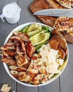 Ensalada de pollo, lascas de queso Grana Padano, aguacate y costrones de pan.