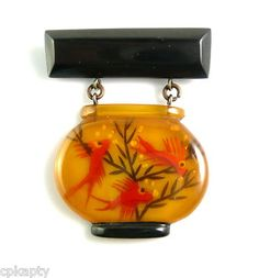 1930s-40s applejuice and black Bakelite fishbowl pin -- fish and greenery are reverse carved and hand painted.