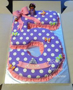 Number 5 Dora the Explorer Birthday Cake by Kristy's Custom Creations.  Yellow cake with homemade buttercream. Covered in purple marshmallow fondant with white mmf polka dots, and a pink mmf ruffle border. Bow, sash with name on it, and Dora's dress are all made out of gum paste. Candy butterflies were also added and I brushed on white/iridescent shimmer dust to make the whole cake sparkle.