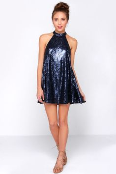 Dance like no one is watching in the Mardi Gras Navy Blue Sequin Halter Dress! This fun-loving trapeze dress is covered in small dark blue sequins, with a subtle ornate design as a hidden surprise. Halter neckline secures with two mother of pearl buttons above a back cutout. Fully lined. 100% Polyester. Hand or Machine Wash Cold.
