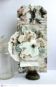 """""""It's so easy to make a tag or a card using the Vintage Floral collection together with the Traveler's Journal products. For this tag I layered some of the ephemera on top of each other ,and then added the cluster to a base cut from one of the Vintage Floral papers. The pale blue and mint are a perfect match to the tea-colored neutrals for a fresh summer look!"""" ~ Riikka"""