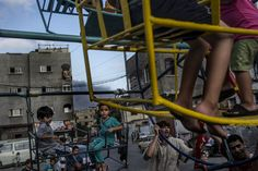 Smoke billows in the background from the site of an Israeli strike as Palestinian children play on a mini ferris wheel in the northern Gaza Strip town of Beit Lahiya.  -- July 29, 2014