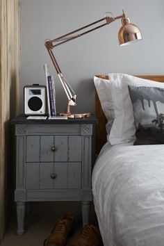 Distressed bedside table and metallic lamp
