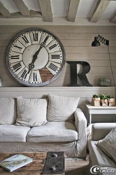 having the large items in the room makes the cieling seem really low. This creates a cozy feel without it being inconvenient. Love the clock too artfully done! The couch look comfy!!!!
