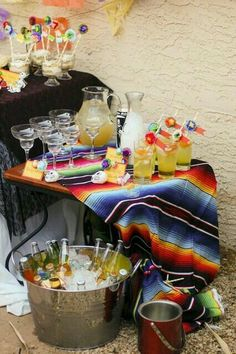 Fiesta beverage station with a serape tablecloth. Fiesta wedding inspiration.