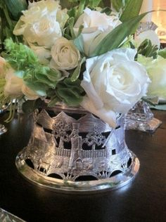 White roses in a silver dish ring.  The dish rings kept hot plates off dining room tables.