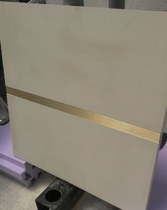 Granite solutions #3: In same manner as this Concrete floor tiles with brass inlay: run bronze inlay over top and profile edges of slab, add bronze detail to bookshelf section