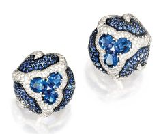 Jayne Wrightsman ,Platinum, Sapphire and Diamond Earclips, Verdura $34,375.00.bombé form, centered by six oval-shaped sapphires, accented by numerous round sapphires weighing 9.45 carats and numerous round diamonds weighing 4.53 carats, gross weight approximately 32 dwts, signed Verdura.