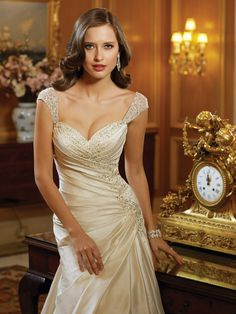 This Sophia Tolli dream taffeta wedding dress with cap sleeves features a hand-beaded A-line and a crystal brooch at the top of a chapel length train.
