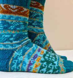 Pacific Rim Socks feature playful sea creatures swimming across horizontal bands. Use this knitting sock pattern as an opportunity to use up all those lovely colored yarns in your stash. The sock is knitted cuff down with an eye of partridge heel. Click through to purchase. #seacreatures #dolphins #turtles #KunstwerkDesigns #cuffdown