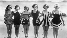 Circa 1929: A row women showing off some unusual and original swimwear on the beach. From Before the Bikini: Rare Vintage Beach Photos