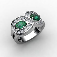 What an exciting ring! Two oval emeralds on either side and round diamonds set in share prongs making a figure eight around each emerald, one of my more unique creations.