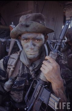 Manuel Moya of a 173rd Airborne U.S. Army Long Range Reconnaissance Patrol as he sits camouflaged in a helicopter in War Zone C during Operation Junction City in the Vietnam War, Tay Ninh Province, South Vietnam (February 1967). Note that he is armed with a CAR-15 rifle.