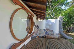 Terraza delantera con sillón de mosaico y ventana redonda. Si quieres ver más, visita OneDreamArt.com