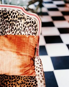 Black and white floor, leopard fauteuil, and a pop of coral...