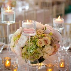 Blush linens were topped with lush centerpieces, votive candles and tall floating candles to create a romantic ambience.
