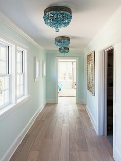 small hallway ideas, hall with pale duck's egg blue walls, windows with white windowpanes, mirror in ornate golden frame, three blue crystal chandeliers, pale wooden floor