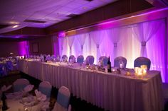 Purple and soft white uplighting created a beautiful backsplash behind the head table at our #wedding. Uplighting by Music 2 Remember in Milwaukee, WI.