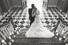 Photo by Kimberly Potterf | Dramatic black and white photo of a bride and groom on a staircase at the Ohio Statehouse surrounded by candles, bride is wearing a beaded fit and flare Lazaro bridal gown, shot is from overhead and showcases the dramatic black and white checkered floor and large doors.