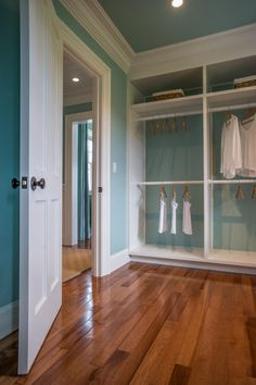 Coastal blue walls combined with stately white crown molding and custom storage units deliver a luxurious finish in this master closet.