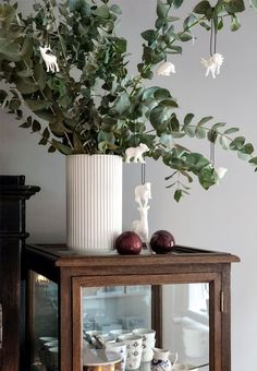 Pretty Christmas decoration made with eucalyptus branches with hanging white Christmas ornaments.