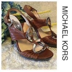 """Michael Kors Heels Beautiful pair of Micheal Kors leather heels.  Soft brown riches and weathered looking straps across foot with incredibly shiny silver ovals with  Micheal Kors engraved on top one, joins straps.  Nice silver buckle.  Dark brown wood grain 4"""" heels with rubber traction sole.  Hardly worn. Michael Kors Shoes Heels"""