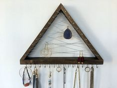 This listing is for one necklace/bracelet/earring organizer. The triangle is approx 10 tall (from the top point to bottom of the hooks) by 13 wide and 1 1/2 deep. There are 16 hooks along the bottom that can be used for bracelets, necklaces or more earrings. This item is available in 9 paint colors and 4 different stains. A 22 gauge wire is twisted in the middle of the triangle. The hooks, nails, and wire are also available in brass and steel finishes. There are 2 hooks on the...