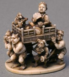 Ivory netsuke depicting four demons carrying a man on litter, man sat crossed legged holding a fan and drinking container accompanied by a small animal. A dog and a monkey are standing either side of the litter both have swords and holding fans. The dog and the monkey are signs of the zodiac. One cord-hole underneath. Marked underneath