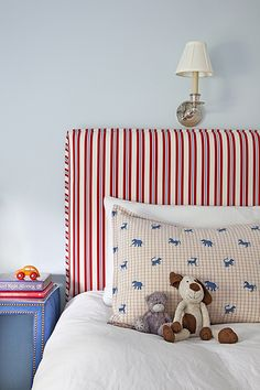 Red, white and blue kid's room with light blue walls framing red and blue striped headboard accented with soft white cotton bedding and safari animals shams next to blue nightstand with silver nailhead trim.