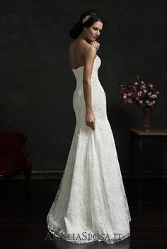 Wedding dress Teofila - AmeliaSposa. The main adornment of this simple dress with a body-clinging fit is not its gorgeous lace, but a bride herself! However, the look may be added with a net with a laced stitchwork. This net like a light veil will hug a body and leave an elegant court train behind.