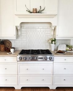 Beautiful range hood along with white cabinets. Timeless space