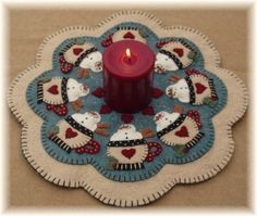 These adorable snowmen are patiently awaiting Santas arrival! This sweet candle mat can be stitched up using wool felt and measures approximately