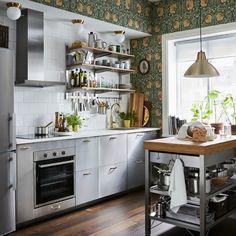 Ett litet kök i brunt och grått med traditionella tapeter och moderna GREVSTA lådfronter i rostfritt stål.
