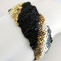 "peyote stitch using Japanese Miyuki delica beads and Toho triangle beads in opaque and matte black, gunmetal, gold, bronze, and silver. It is approximately 1"" wide. Unless you specify otherwise (see SIZING below) the beaded band will be made to 7"" long and the closure adds another 0.5"" to the length of the clasped cuff, providing a comfortable fit on a 7"" wrist."