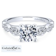 This creative style from Gabriel & Co. features milgrain lined pear-shaped pods along the band loaded with round diamonds. The band leads to the cubic zirconia center stone which can be replaced by a round carat) diamond. This engagement ring c Engagement Rings Cushion, Engagement Ring Buying Guide, Round Diamond Engagement Rings, Diamond Wedding Bands, White Gold Diamonds, Round Diamonds, Fashion Rings, Fashion Jewelry, Thing 1