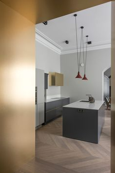 To provide touches of colour, the designer has applied gold-hued sheets of brass to the home's entrance doorway and a singular kitchen cupboard.