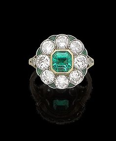 An emerald and diamond cluster ring, circa 1930. The cut-cornered step-cut emerald, within a surround of brilliant-cut diamonds, highlighted with fancy-cut emeralds