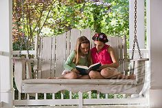 Girls sitting on porch swing reading