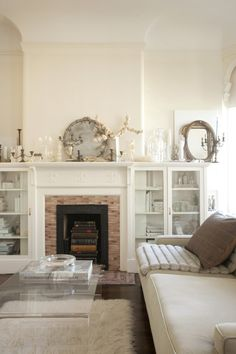 I bought all white furnishings for my living room... what was I thinking? So pretty, but not practical.  I love the cabinets flanking the fireplace...