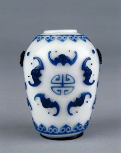 An eighteenth-century Chinese glass vase decorated with five bats, symbolising five blessings, surrounding a 'shou' (longevity) character. (British Museum)